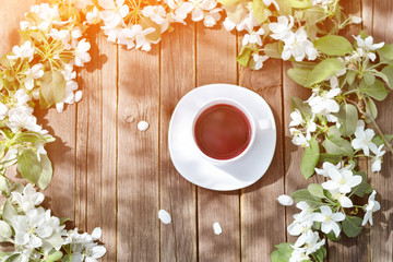 Top view on mug of tea among apple flowers on a wooden background.