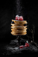 a stack of pancakes decorated with berries and powdered sugar, rustic studio shot, can be used as background