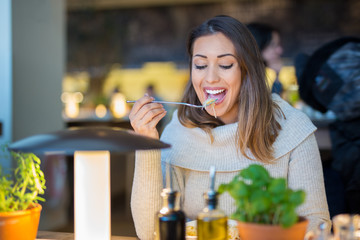 Beautiful woman eating lunch at a restaurant while smiling