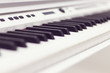 closeup white piano keys, white piano isolated, side view of an instrument. learning to play at home. white grand digital piano. piano keyboard. concert concept. selective focus.