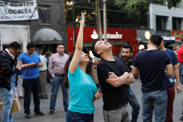 People react during a tremor in Mexico City
