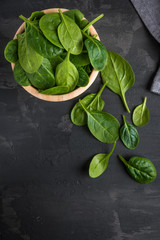 Spinach. Fresh organic spinach leaves in wooden bawl on a wooden table. Diet, dieting concept. Vegan food, healthy eating. Dark rustic style photo.
