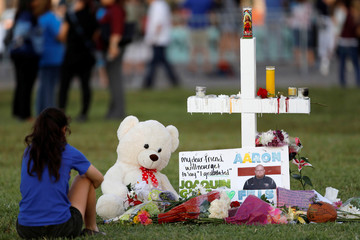 A mourner sits by a cross adorned with pictures of victims, along with flowers and other mementoes, at a memorial two days after the shooting at Marjory Stoneman Douglas High School in Parkland
