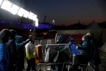 Media members work on as the Olympic cauldron is seen in the background at the Medals Plaza in Pyeongchang
