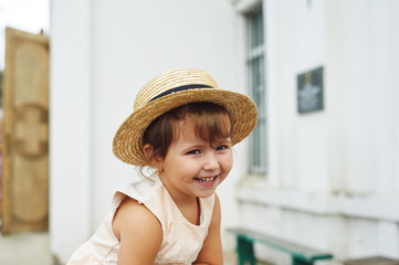 Cheerful little girl in a summer hat on the streets
