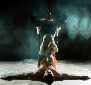 Young sports couple doing acroyoga exercises in a dark room with colorful smoke