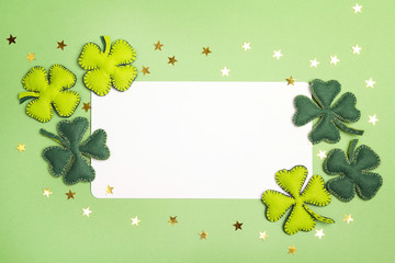 Blank white card with felt leaves of clover on green background. Space for text.