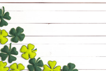 St.Patrick's day background with felt four-leaf clover on white wooden table. Lucky irish shamrock. Space for text,