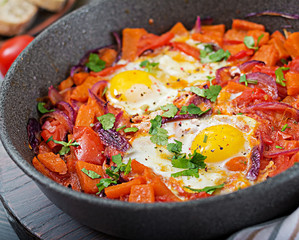 Fried eggs with pieces of pumpkin, red onions and tomatoes. Tasty breakfast.
