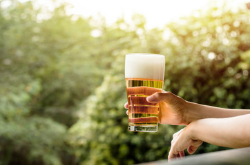 Drinking Beer in Summer Concept. Woman with Glass of Beer on Balcony. Natural Sunlight and Tree as background, Warm Tone