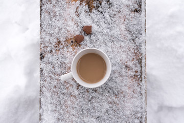 Cup of coffee on a snowy board