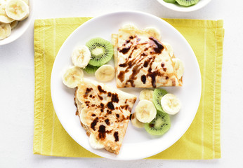 Crepes with banana, kiwi slices and chocolate sauce