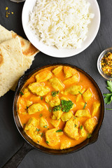 Indian chicken curry on black stone background with copy space. Top view, flat lay