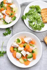 Chicken soup with carrot, broccoli, potato, top view