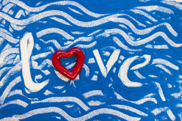 Love inscription on a blue colored sand with waves, top view, flat lay