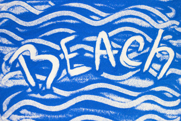 Beach inscription on a blue colored sand with waves, top view, flat lay