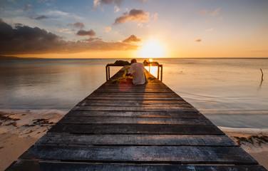 sunset seascape with wooden jetty toward horizon.