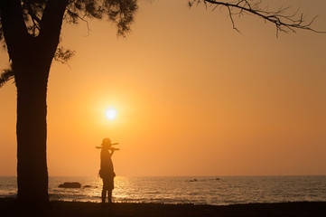 golden sunset with silhouette of unknown man and tree.