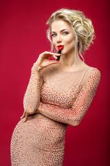 beautiful blond girl putting red lipstick on