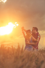 Couple dancing in a wheat field under the sunlight.