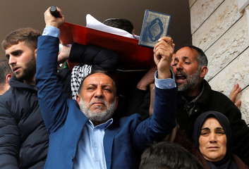 The father and mother of Palestinian assailant Hamza Zamarah, carry his body during his funeral in Halhoul, in the occupied West Bank