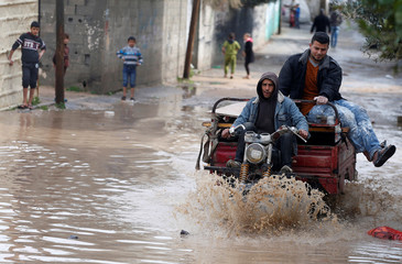 Palestinians pass a flooded street following heavy rains in Beit Hanoun town in the northern Gaza Strip