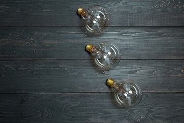 Three edison lamps with a beautiful spiral on a black textured wooden background