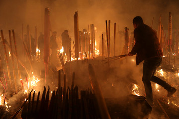 People burn incense sticks and pray for good fortune at Giant Buddhist Temple on the first day of the Chinese Lunar New Year of Dog, in Chongqing