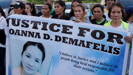 Residents display placards as they wait for the arrival of the body of Joanna Demafelis, a Filipina domestic helper who was killed and found inside a freezer in Kuwait, in her hometown in Iloilo