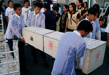 Funeral workers carry a crate containing the body of Joanna Demafelis, a Filipina domestic helper who was killed and found inside a freezer in Kuwait, in her hometown in Iloilo