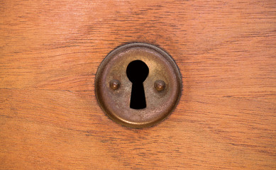 Old rusty and dusty keyhole wallpaper. Vintage keyhole on old wooden door background. Keyhole of old door.