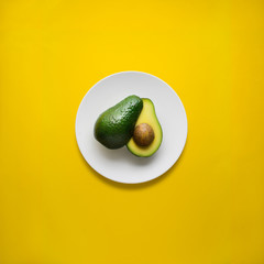 Dinner is served / Creative concept photo of avocado on painted plate on yellow background.