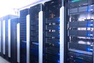 Web network, internet telecommunication technology, big data storage, cloud computing computer service business concept: server room interior in datacenter in blue light.