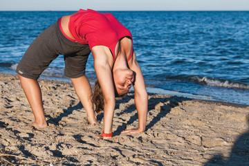 Attractive female student doing gymnastics on beach