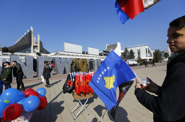 """Street vendor holds flag in front of the """"Newborn""""  monument updated for celebrations of the 10th anniversary of Kosovo's independence in Pristina"""