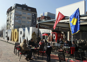 """People sit in coffee shop near the """"Newborn"""" monument updated for celebrations of the 10th anniversary of Kosovo's independence in Pristina"""