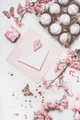 Beautiful pastel pink Easter greeting card mock up with blossom decoration, hearts, eggs in carton box on white desk background, top view, flat lay.