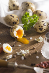 Quail egg arranged on wooden table with salt and pepper parsley sprig