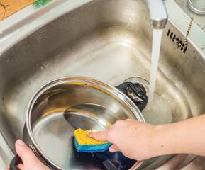 Frau verschwendet Wasser beim Geschirrspülen