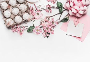 Pastel pink Easter greeting card mock up with blossom decoration, feathers, eggs in carton box on white desk background, top view, flat lay, border, close up