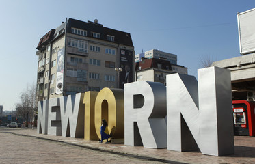 """Girl girl covered with Kosovo flag walks in front of the """"Newborn"""" monument updated for celebrations of the 10th anniversary of Kosovo's independence in Pristina"""