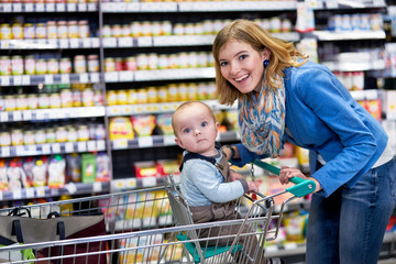 Happy young woman with toddler in grocery store