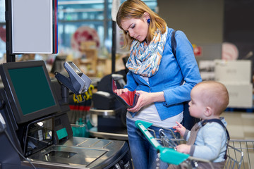 Young woman with baby paying with self checkout