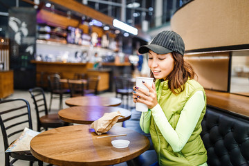 Young woman drinking coffee from disposable cup in cafe