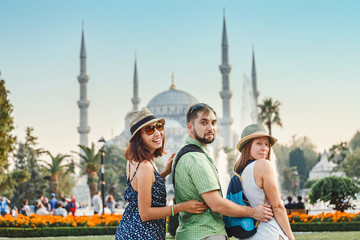 Group of Friends hugging and looking at Istanbul great Blue Mosque. Student travel in Turkey concept
