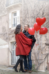 love story. A young man and a young woman with red accessories are walking in the city