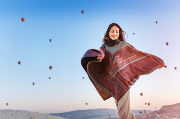 Woman having a good time in Cappadocia at the background of hot air balloons