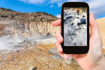 tourist photographs mud acidic geyser in Iceland
