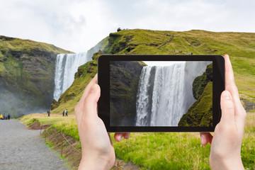 tourist photographs Skogafoss waterfall in autumn