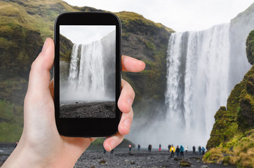 tourist photographs Skogafoss waterfall in Iceland